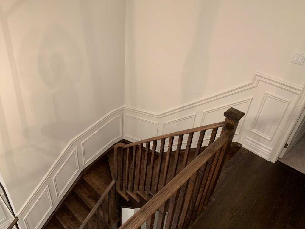 staircase with wainscoting wall trim
