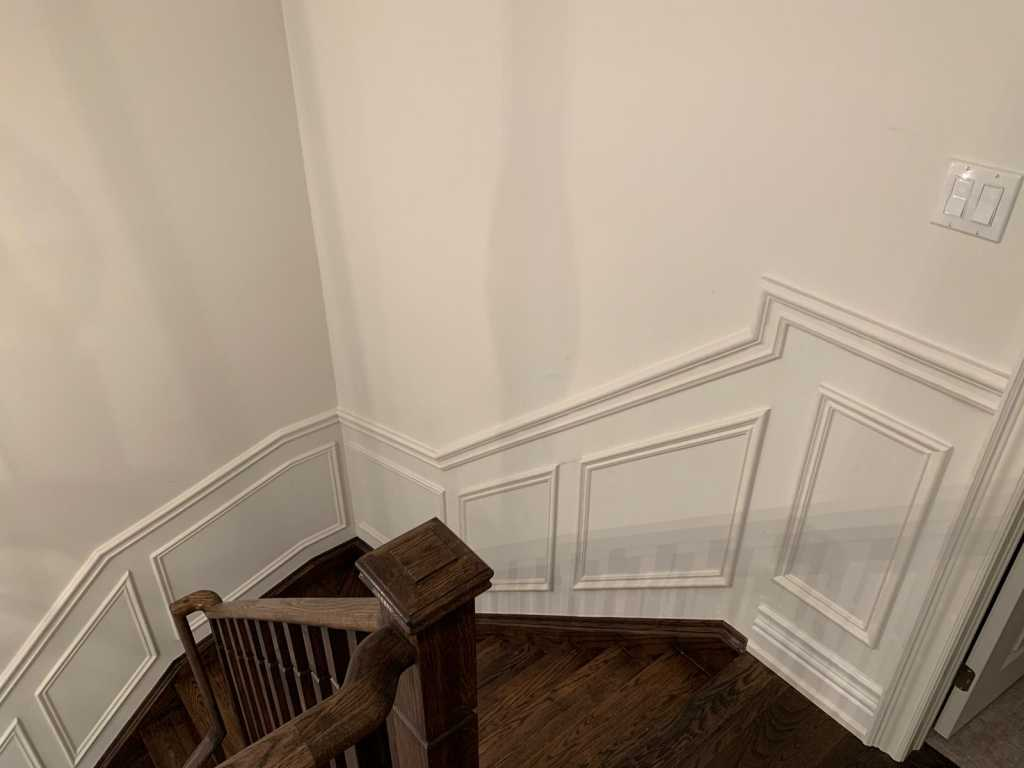 luxury staircase with wainscoting wall trim