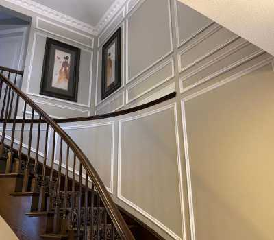 luxury stair case with coffered wall decor