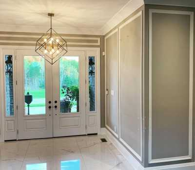 front door hallway with coffered wall decor