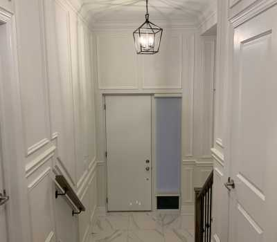 hallway with cofferd wall decor and crown moulding